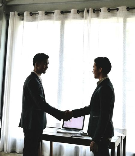 Businessmen shaking hands while standing in office
