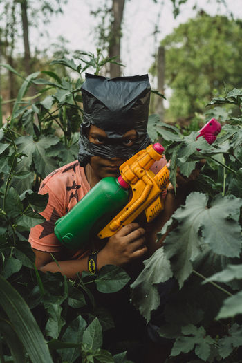 Portrait of boy holding water gun amidst plants