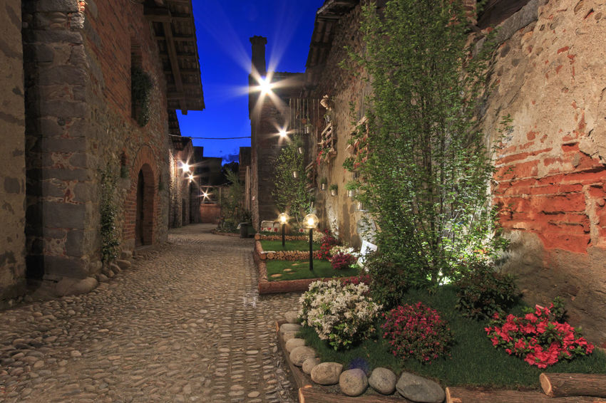 Candelo, Biella - May 4, 2016: View form the inside of the Medieval village of Ricetto di Candelo in Piedmont, used as a refuge in times of attack during the Middle Age. Architecture Biella Blue Built Structure Candelo Candelo In Fiore Day Diminishing Perspective Empty Footpath Illuminated Italy Lens Flare Long Medieval Village Narrow No People Outdoors Pathway Ricetto Di Candelo  Sunlight Sunny The Way Forward Vanishing Point Walkway