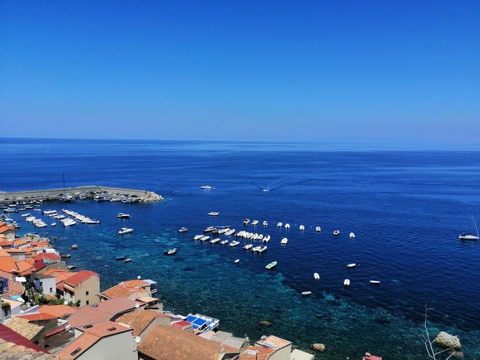 Scenic angle view of sea against clear blue sky