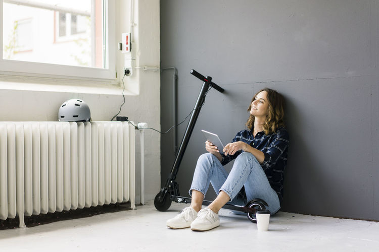 Woman using phone while sitting on laptop