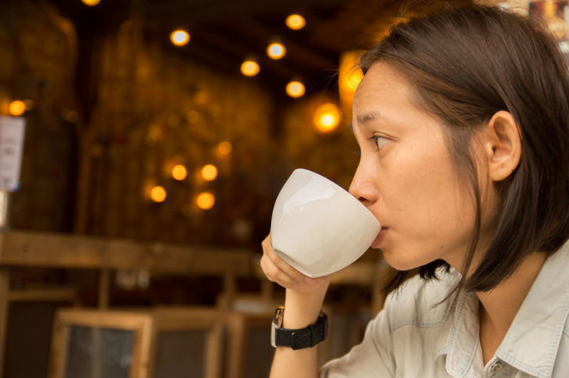 Asian woman drinking from coffee cup in cafe