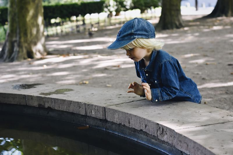 Rear view of boy sitting in park