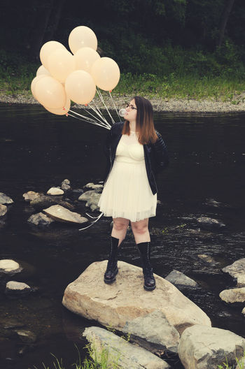Woman Blowing Bubble Gum While Standing On Rock At Lake