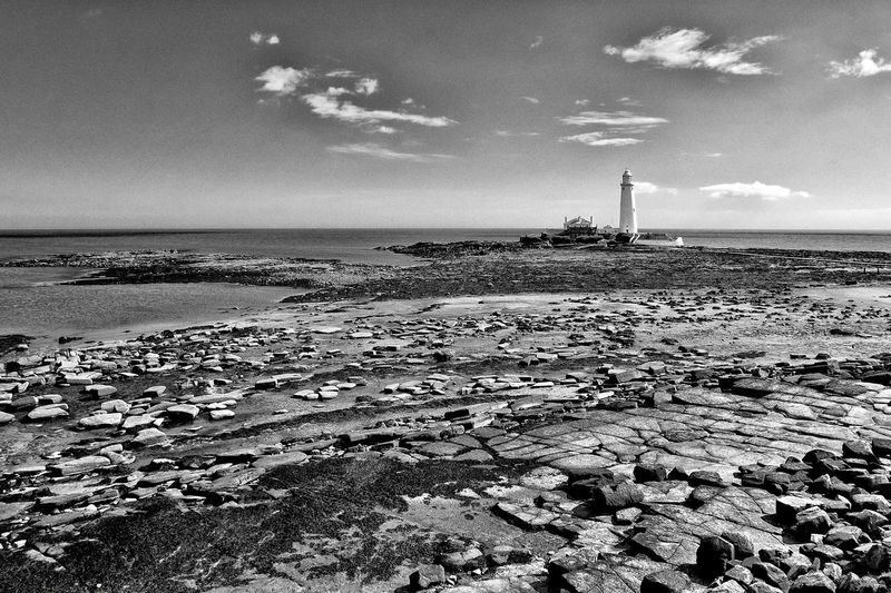 ST MARY'S LIGHTHOUSE AT LOW TIDE: Built in 1897-1898 to the design of J. Livingstone Miller of Tynemouth, the lighthouse stopped working in 1984. It's now a visitors' centre. Whitley Bay, Tyne and Wear. Viewed across the exposed sedimentary rocks of the Pennine Coal Measures. Coal Low Tide Lighthouse Monochrrome Architecture Beach Beauty In Nature Cloud - Sky Day Horizon Over Water Land Nature No People Outdoors Rock Rock - Object Scenics - Nature Sea Sky Surface Level Tranquil Scene Tranquility Water Non-urban Scene Rock Formation Tall Seascape Rocky Coastline