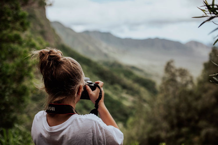 Rear view of woman photographing against mountains