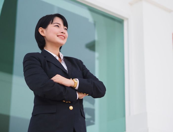 Young Asian business woman smiling in front of building. Black Hair Business Business Woman Communication Day Freshness Indoors  Occupation One Person Smiling Student Suit University Student Well-dressed Women Young Adult