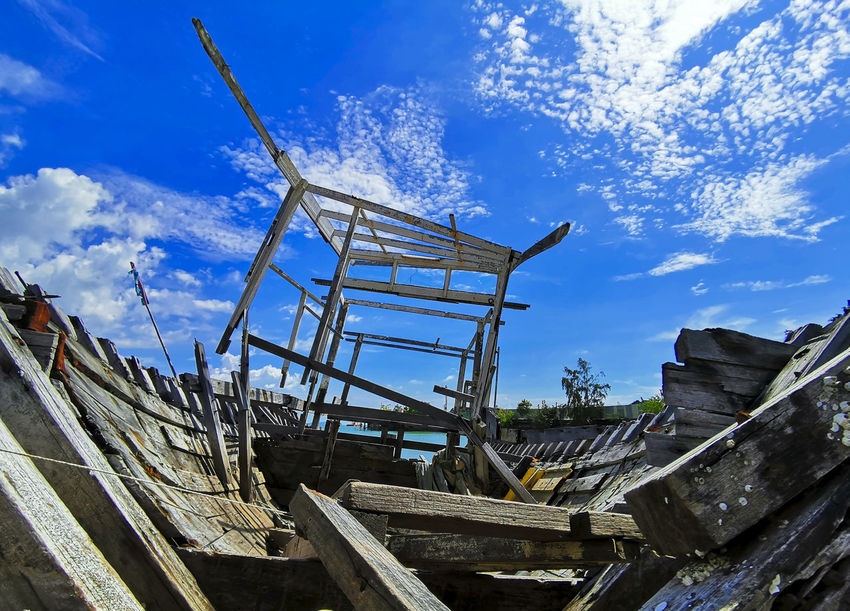 Damage wooden boat frame at the beach with beautiful blue sky Day Nature No People Outdoors Damaged Object Old Barn Blue Sky Women Rotterdam Beach Photography Color Sand Sunrise