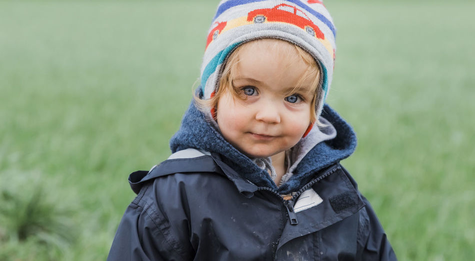 Happy toddler girl in front of field – Kempen, Germany Baby Babyhood Beautiful Beauty Blond Blue Eyes Carefree Casual Caucasian Cheerful Child Childhood Close-up Coat Confidence  Contemplation Content Curiosity Cute Daydreaming Dirt Emotion Expression Face Field Front View Germany Girl Grass Happy Headshot Innocence Jacket Joy Knit Hat Looking At Camera Messy Nature One Outdoors People Portrait Positive Rural Smiling Standing Toddler  Waist Up Watching Winter Clothing One Person Warm Clothing Focus On Foreground Day Hat