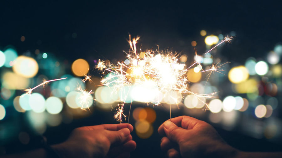 Cropped hands holding sparklers