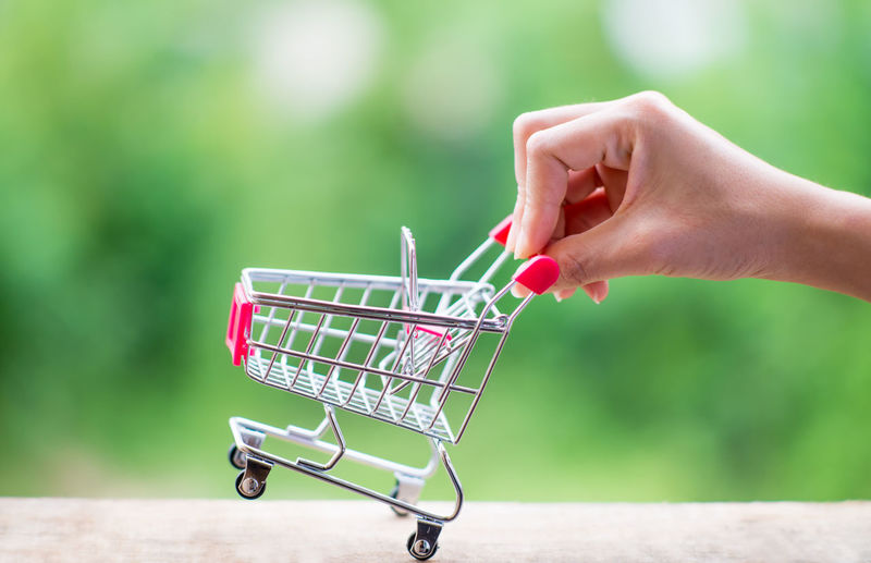 Close-Up Of Person Hand Holding Shopping Cart On Table