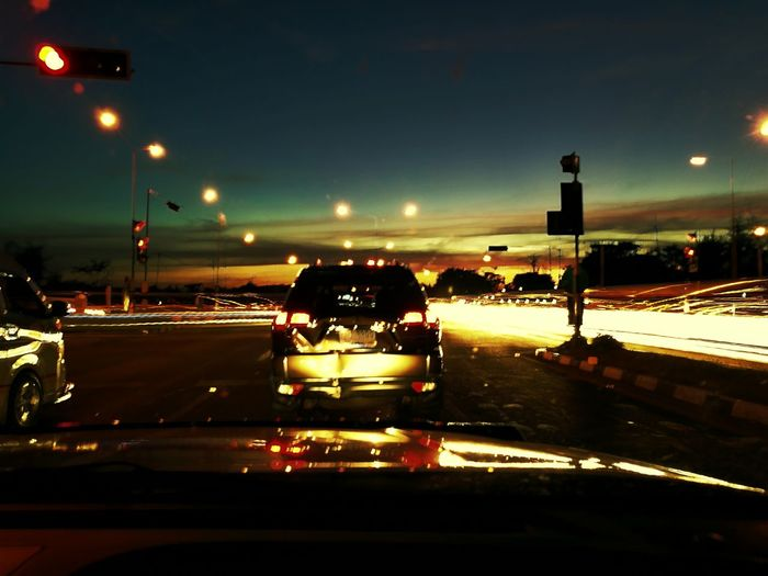 Cars on road against sky at night