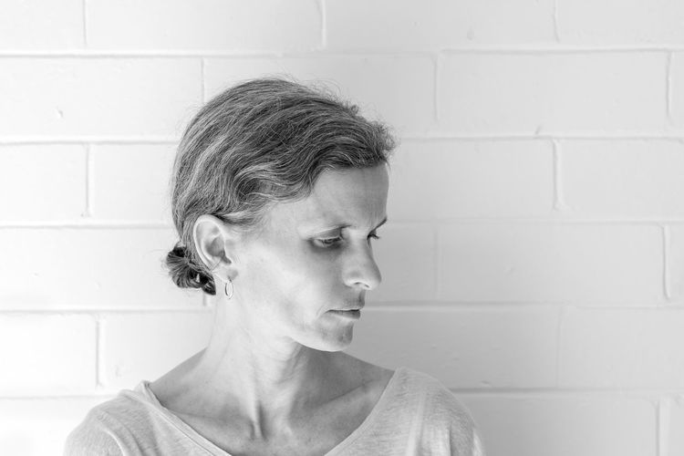 Middle aged woman (black and white) Headshot One Person Portrait Wall - Building Feature Lifestyles Looking Close-up Real People Looking Away Indoors  Adult Leisure Activity Front View Wall Women Casual Clothing Emotion Human Body Part Contemplation Human Face