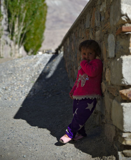 Full length of a girl standing against stone wall