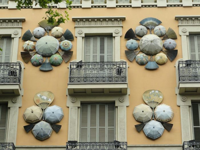 Sculpture Of Umbrellas And Fans On Wall Between Two Shuttered Balconies