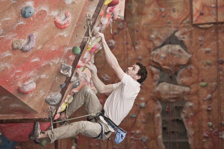 Full length of man climbing on wall