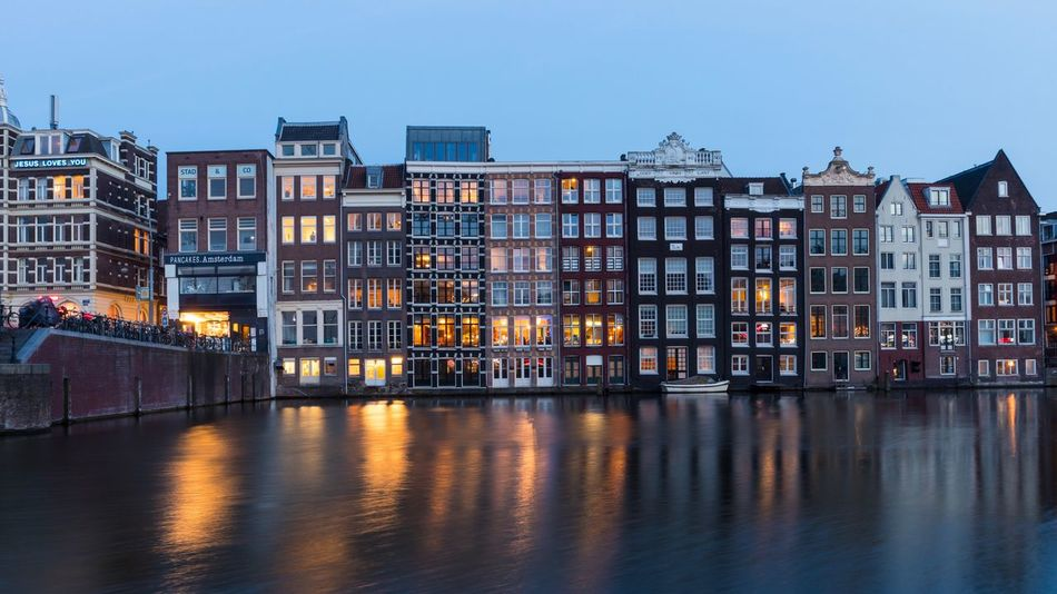 Looking at buildings of Warmoesstraat Classic Architecture Typical Dutch The Netherlands Holland Cityscape Amsterdamse Grachten Amsterdam Houses Amsterdam By Night Amsterdam Canal Amsterdam Architecture Building Exterior Built Structure House Residential Building Outdoors Night