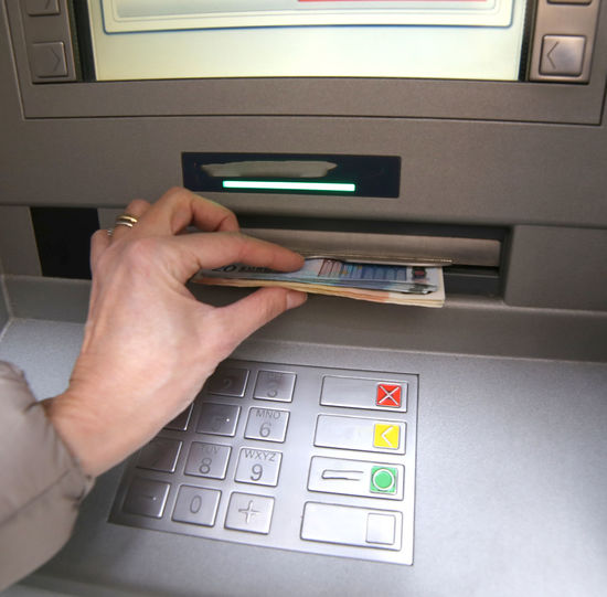Cropped hand of woman withdrawing cash from atm