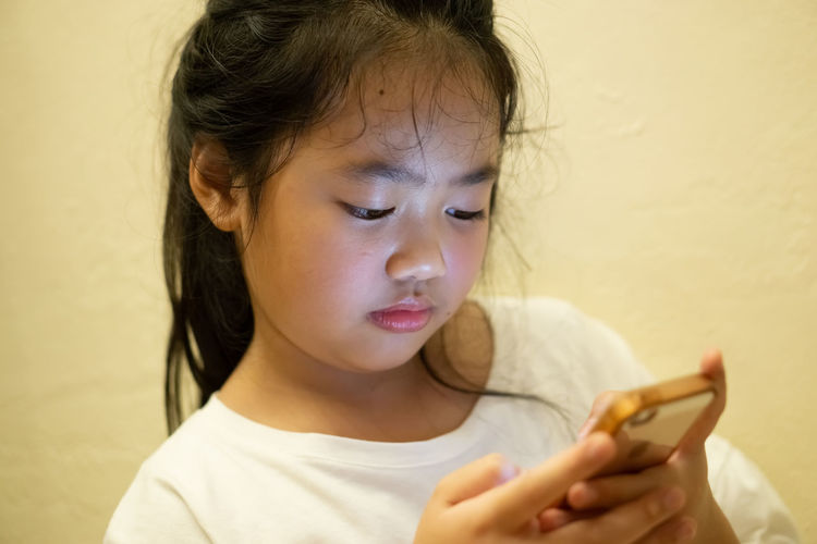 Portrait of cute girl holding smart phone
