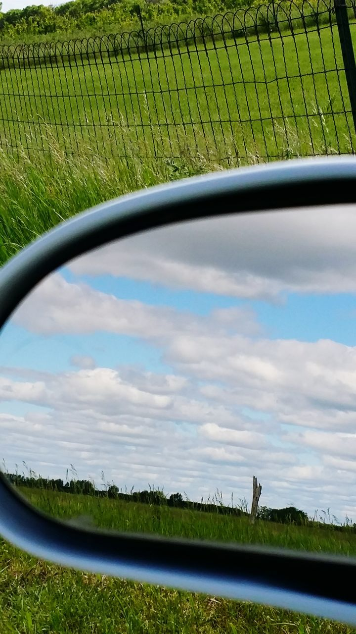 grass, side-view mirror, green color, field, reflection, no people, nature, sky, day, landscape, transportation, outdoors, land vehicle, beauty in nature, water, growth, tree