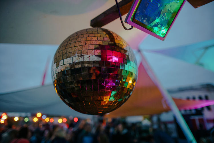 photo of disco ball with incidental people in the background Disco Ball Reflection Sphere Focus On Foreground Close-up Incidental People Arts Culture And Entertainment Hanging Multi Colored Low Angle View Shiny Outdoors Nightlife Mid-air Transparent Day Glass - Material Decoration