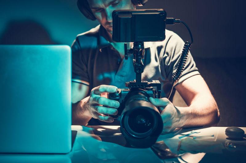 Man holding camera in darkroom