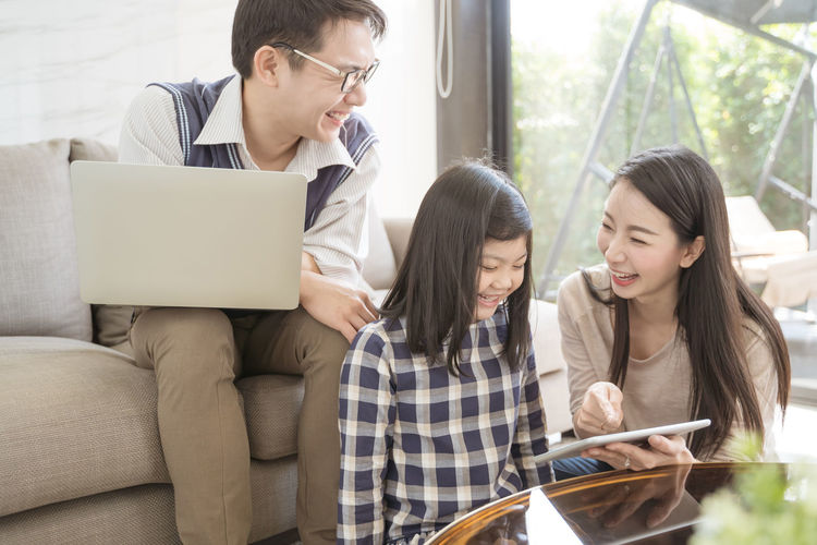 happy asian family spending time together on sofa in living room. family and home concept Asian  Family Happiness Happy Happy People Family Time Home House Daughter Parent Father Mother Dad Mom Love Lifestyles Living Room ASIA Japanese  Korean Thai Taiwan Portrait Internet Lerning Tablet Technology Laptop Digital Digital Tablet Smiling Smile Fun Girls