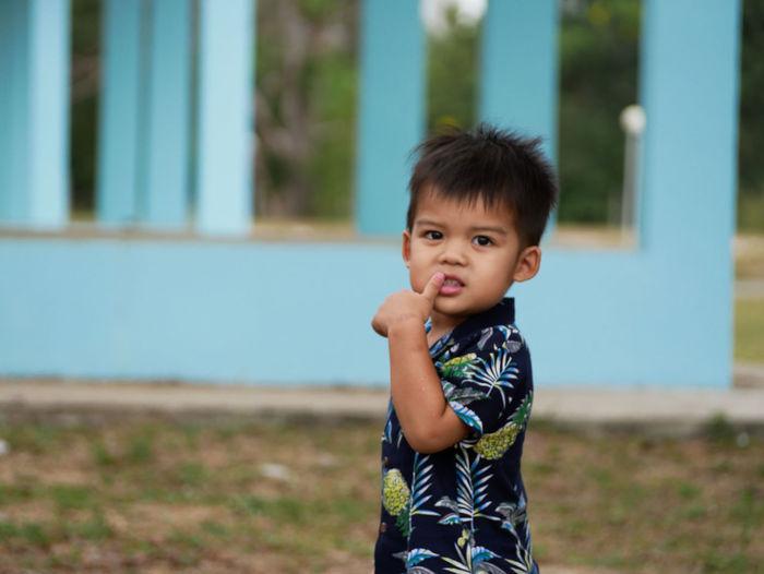 Portrait of cute boy standing on grass