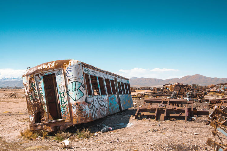 Old abandoned train on field against blue sky during sunny day