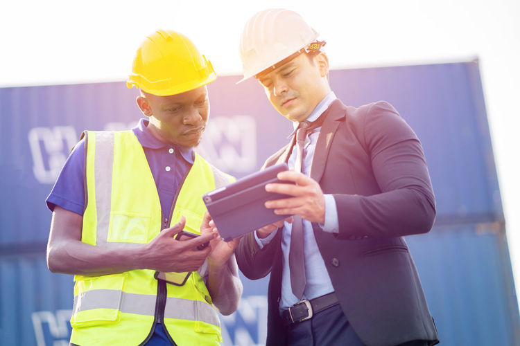 Midsection of man working with mobile phone