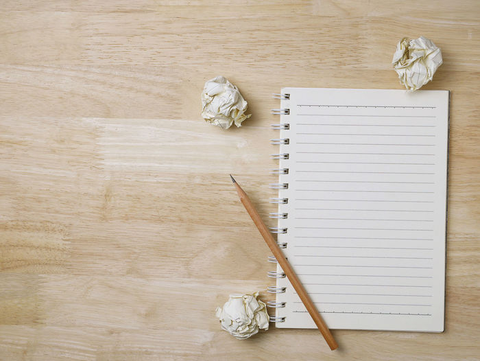 Pencils Blank Book Close-up Copy Space Crumpled Paper Ball Directly Above High Angle View Indoors  No People Note Pad Page Paper Pen Pencil Plant Publication Spiral Notebook Still Life Table White Color Wood - Material