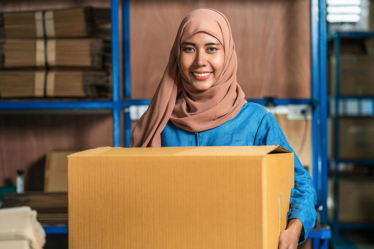 Portrait of smiling young woman holding cardboard box