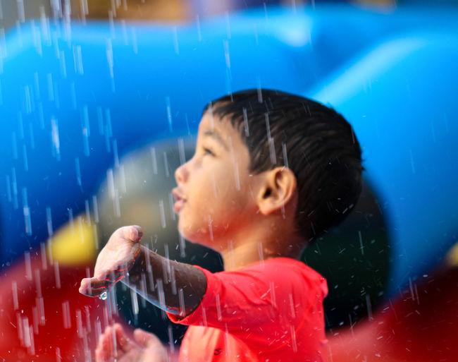 Cute boy touching rain water
