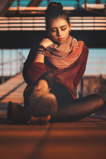 Young woman looking away while sitting on floor