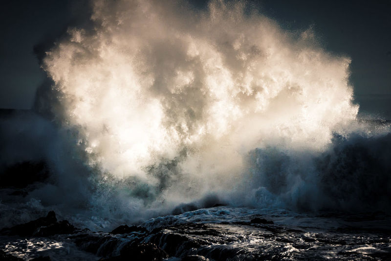 Waves splashing in sea against sky