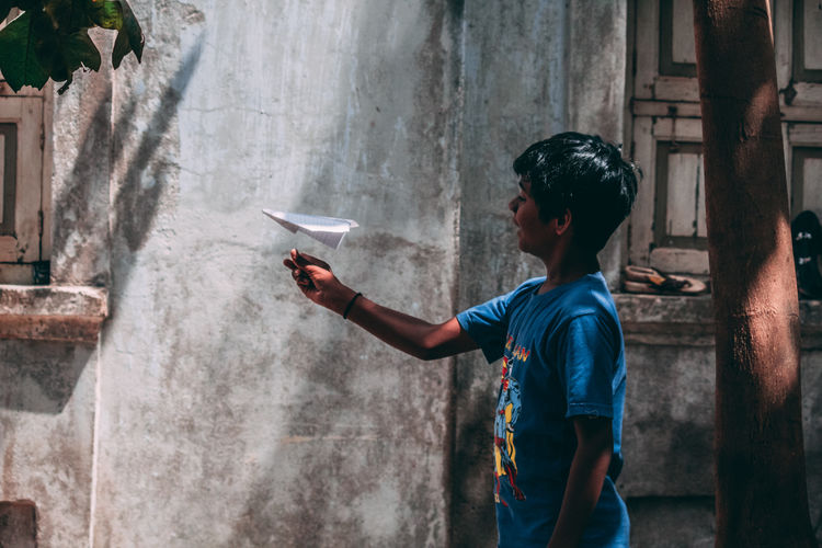Boy playing with paper airplane against wall