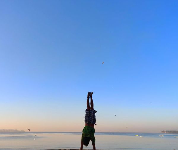 Full length of man practicing handstand at beach against clear sky during sunset