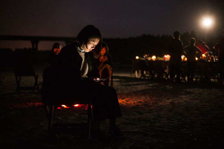 Adult Bonfire Casual Clothing Field Focus On Foreground Full Length Illuminated Incidental People Land Leisure Activity Lifestyles Nature Night Outdoors People Real People Sitting Sky Women Young Adult Young Women