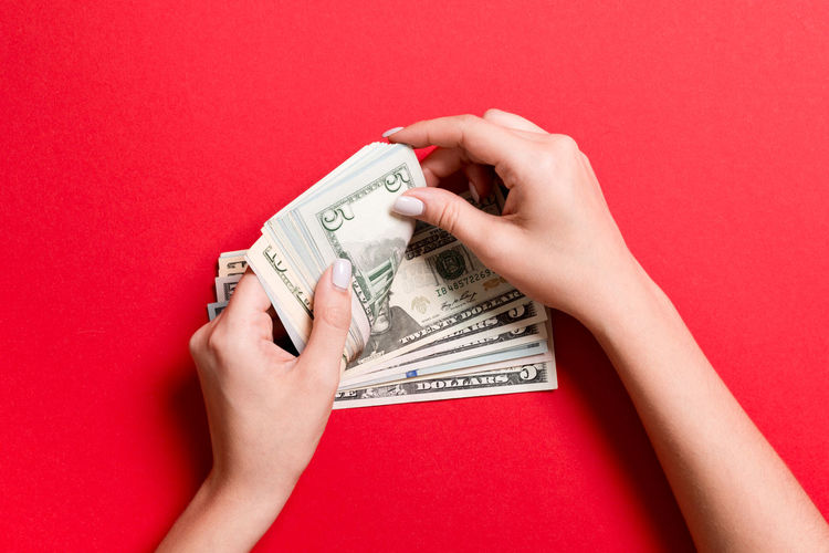 Midsection of person holding paper against red background
