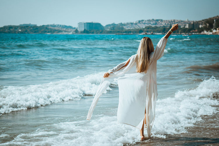 Adult Beach Beautiful Woman Beauty In Nature Hair Hairstyle Human Arm Land Leisure Activity Lifestyles Long Hair Motion Nature One Person Outdoors Real People Sea Standing Water Women Young Adult