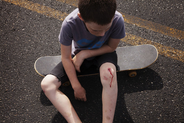 High angle view of boy sitting on road