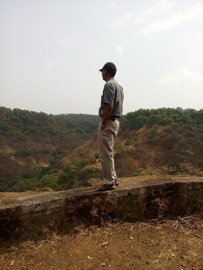 Rear view of man standing on streetside wall looking towards forest