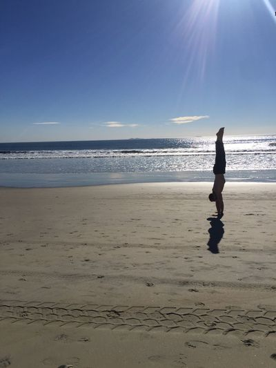 Man doing handstand at beach during sunset