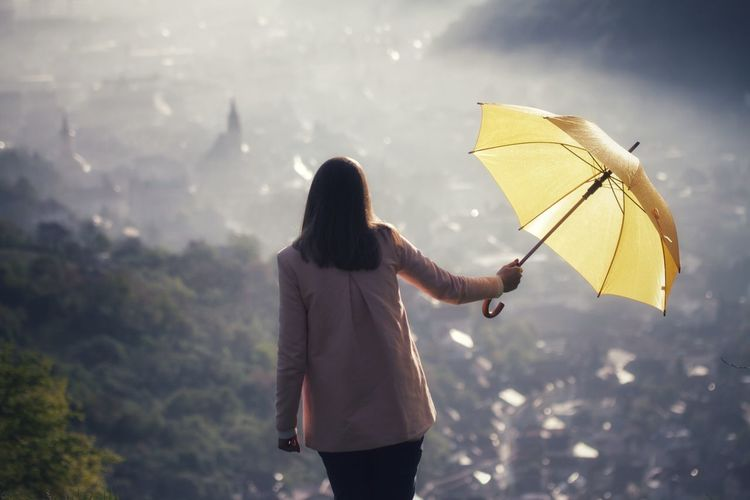 Rear view of woman holding umbrella against mountain