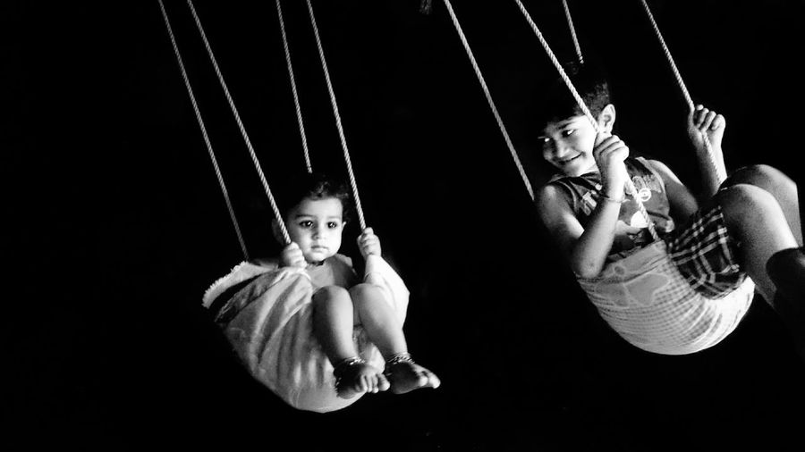 Siblings in swing against black background