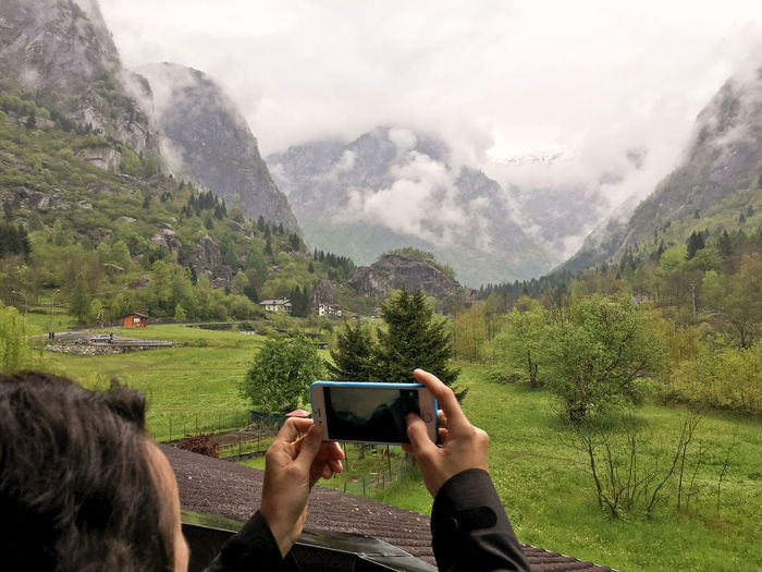 Cropped Image Of Man Photographing Field And Mountains