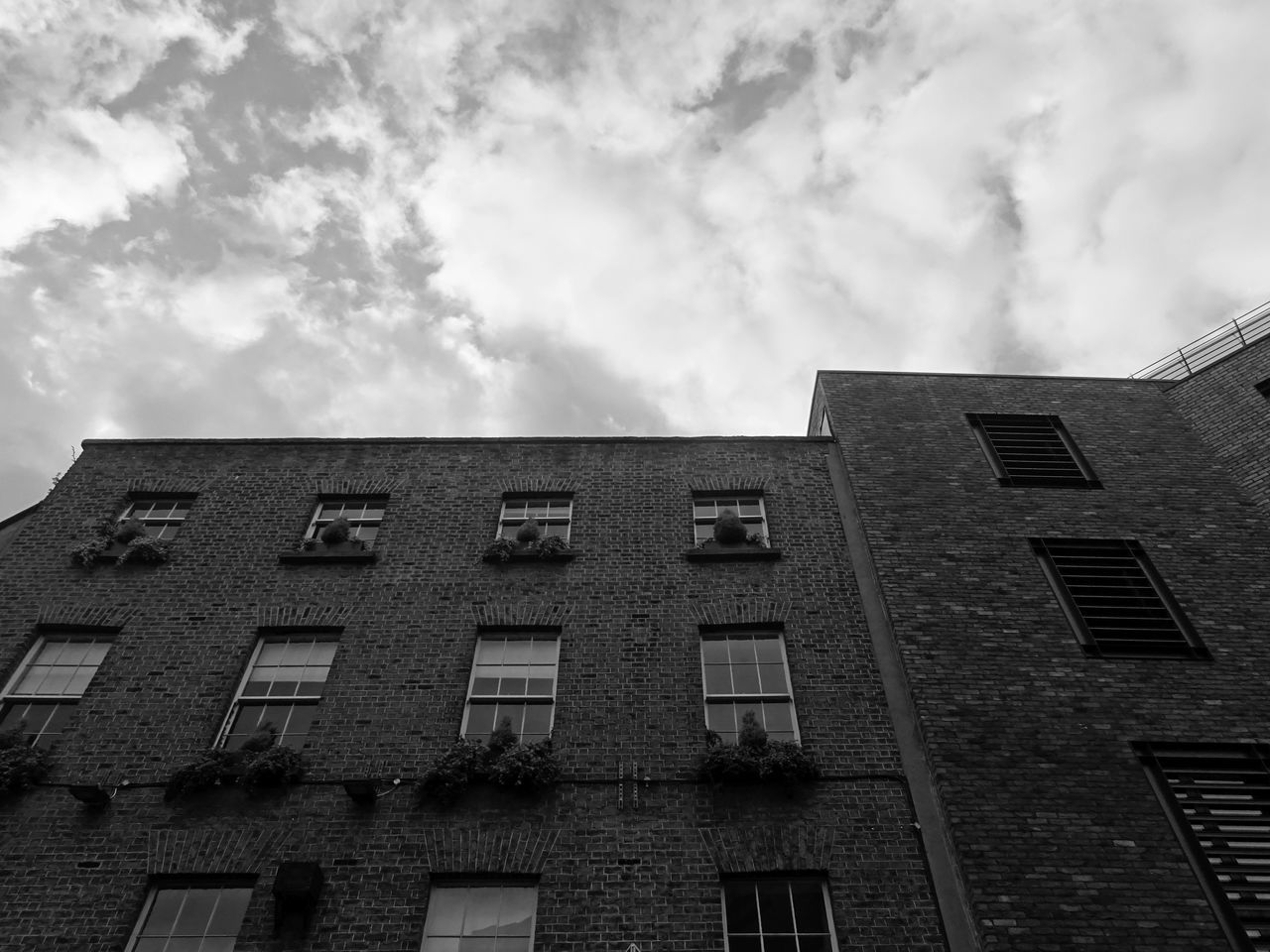 cloud - sky, building exterior, sky, built structure, architecture, window, low angle view, building, residential district, no people, city, nature, day, outdoors, overcast, repetition, apartment, in a row, old