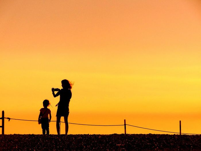 Mother & Child take a Picture during sunset Silhouette