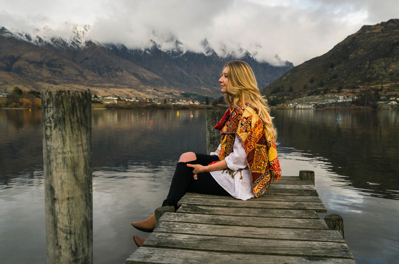 Beauty In Nature Casual Clothing Cloud - Sky Day Full Length Lake Leisure Activity Lifestyles Mountain Mountain Range Nature One Person Outdoors Pier Real People Reflection Relaxation Scenics Sitting Sky Standing Tranquility Water Young Adult Young Women