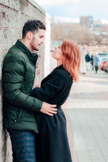 Side view of young couple standing in city